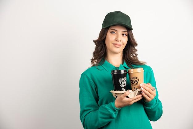 Weiblicher kurier in uniform mit kaffeetassen.