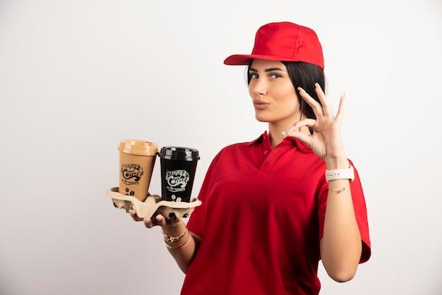 Weiblicher kurier mit kaffee, der ok zeichen zeigt. hochwertiges foto