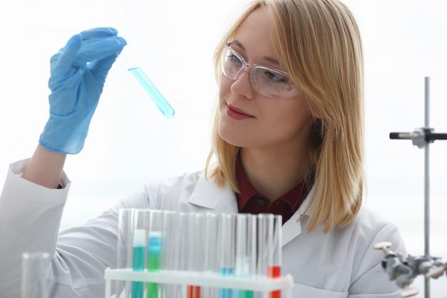 Weiblicher laborarbeiter, der reagenzglas mit giftflüssigkeit hält