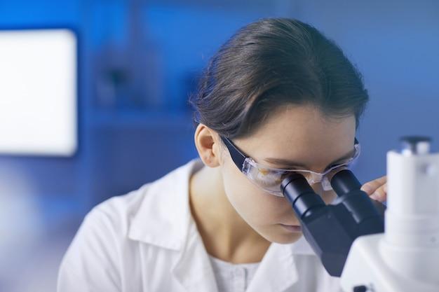 Weiblicher labortechniker, der im mikroskop schaut