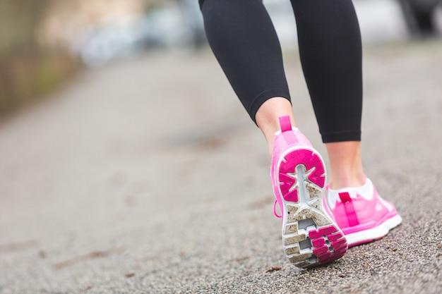 Weiblicher läufer beschuht nahaufnahme auf der straße, stadteinstellung. geringe schärfentiefe, fokus auf den hinteren schuh.