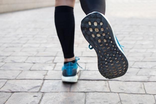 Weiblicher läufer, der auf der straße läuft