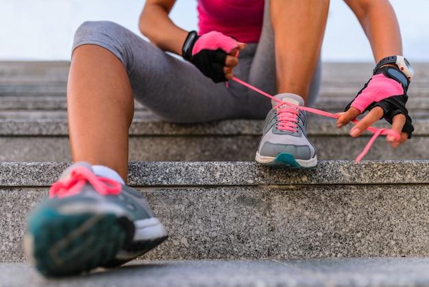 Weiblicher läufer, der ihre schuhe bindet