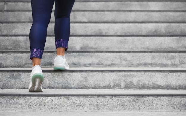 Weiblicher läuferathlet, der das treppenklettern tut.