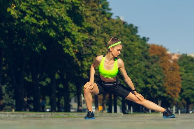 Weiblicher läuferathlet, der draußen im sonnigen tag des sommers trainiert