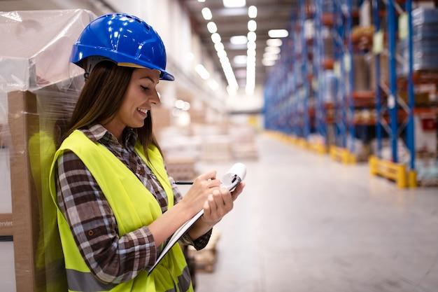 Weiblicher lagerarbeiter, der sich auf pappkartons stützt und notizen im großen lagerverteilungszentrum macht