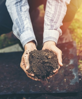 Weiblicher landwirt, der boden bepflanzbar hält, pflügte schmutz in schalenförmigen händen