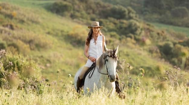 Weiblicher landwirt, der draußen reitet