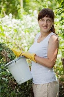 Weiblicher landwirt, der gras kompostiert