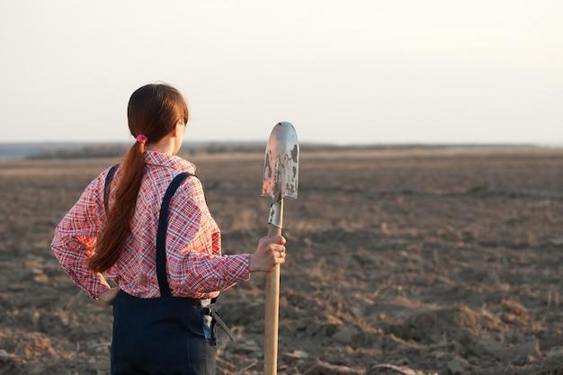 Weiblicher landwirt im gepflügten feld