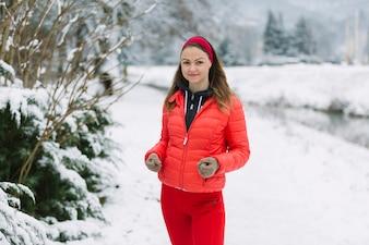 Weiblicher Läufer, der im Schnee rüttelt