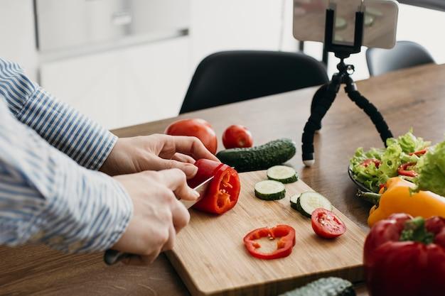 Weiblicher lebensmittelblogger, der mit smartphone zu hause beim kochen strömt