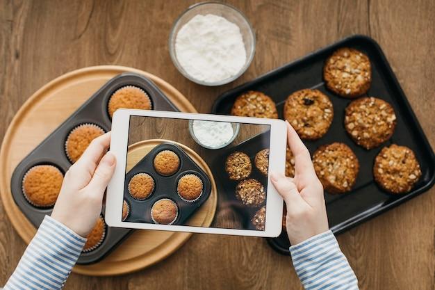 Weiblicher lebensmittelblogger, der mit tablette zu hause beim kochen strömt