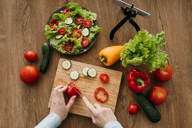 Weiblicher lebensmittelblogger, der zu hause beim kochen mit smartphone strömt