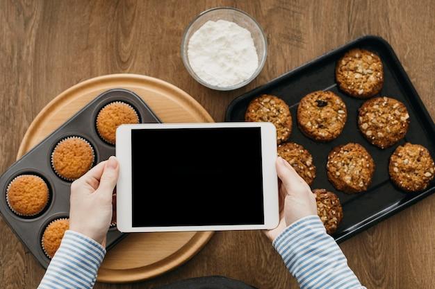 Weiblicher lebensmittelblogger, der zu hause beim kochen mit tablette strömt