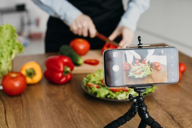 Weiblicher lebensmittelblogger, der zu hause beim kochen strömt