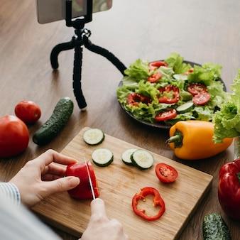 Weiblicher lebensmittelblogger, der zu hause mit smartphone beim kochen strömt