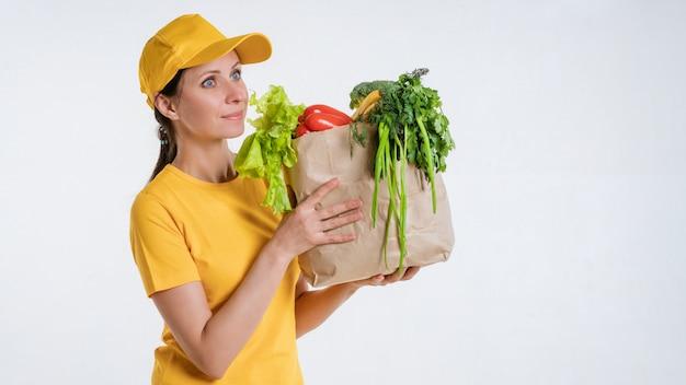 Weiblicher lebensmittellieferant mit lebensmittelpaket