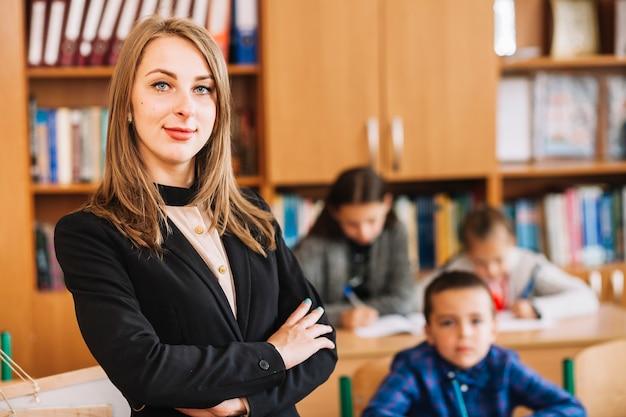 Weiblicher lehrer auf unscharfem hintergrund des klassenzimmers