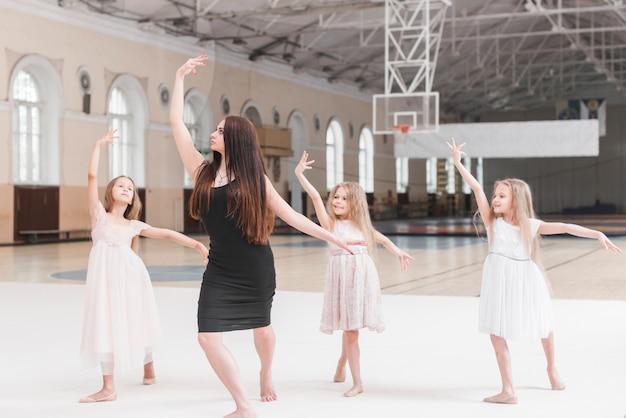 Weiblicher lehrer, der ballerina-tanztraining zu drei mädchen gibt