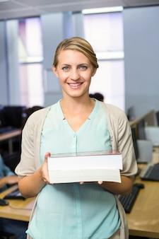 Weiblicher lehrer, der bücher in der computerklasse hält