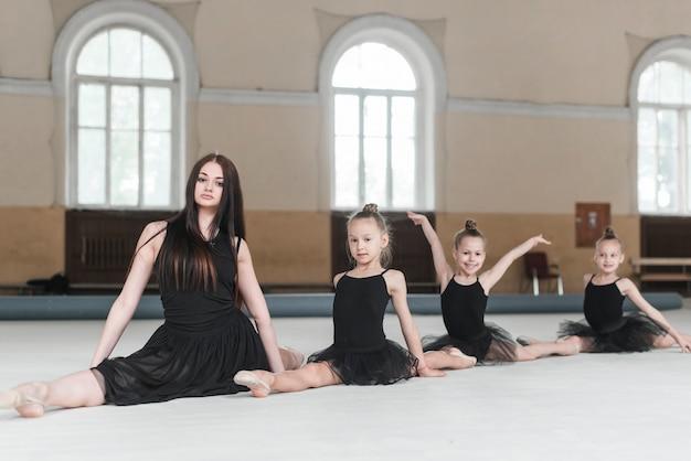 Weiblicher lehrer, der mit drei mädchen auf boden in der tanzklasse sitzt
