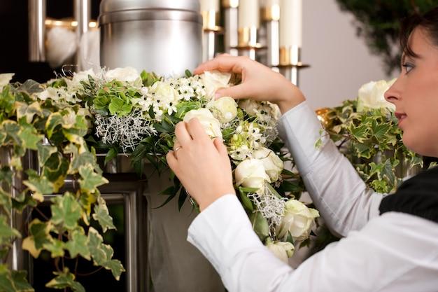 Weiblicher leichenbestatter, der urne begräbnis vorbereitet