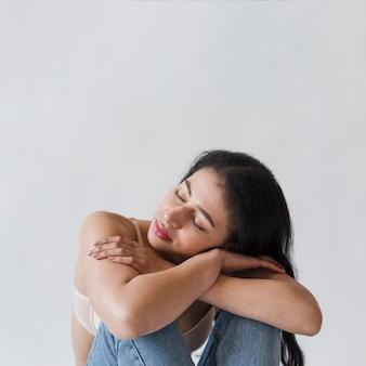 Weiblicher lügenkopf auf den armen gefaltet auf knien