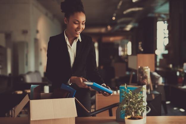 Weiblicher manager legt sachen auf arbeitsplatz aus