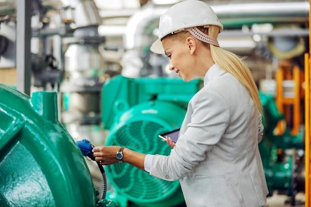 Weiblicher manager mit helm, der im heizwerk mit tablette in den händen steht und auf turbine prüft.