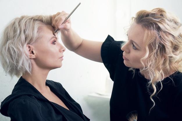 Weiblicher maskenbildner, der ein make-up für ein junges blondes modell vor einer fotosession macht. visagiste bearbeitet augenbrauen oder eine stirn des schönen mädchens mit einem pinsel.