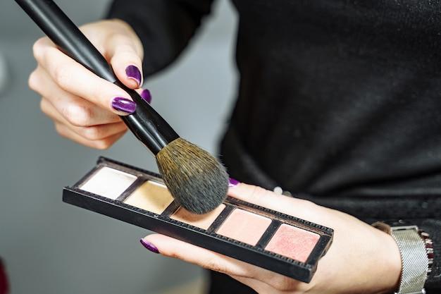 Weiblicher maskenbildner mit kosmetik bei der arbeitsnahaufnahme