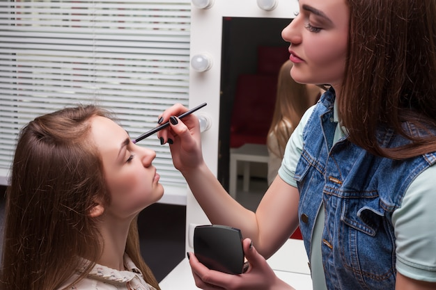 Weiblicher maskenbildner mit pinsel in den händen, die make-up auf schönem mädchengesicht, schönheitsstudio auf hintergrund anwenden. kosmetischer salon