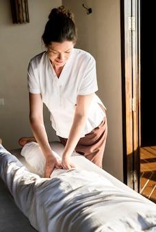 Weiblicher massagetherapeut, der eine massage an einem badekurort gibt
