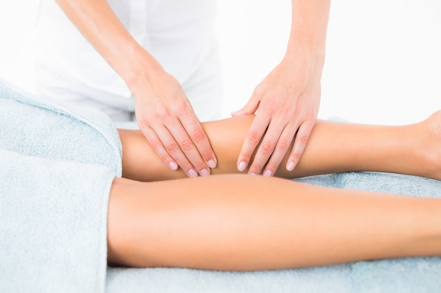 Weiblicher masseur, der das bein der frau massiert