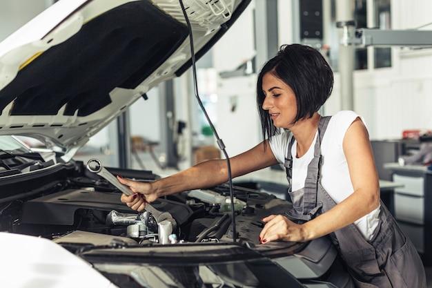 Weiblicher mechaniker, der am service arbeitet