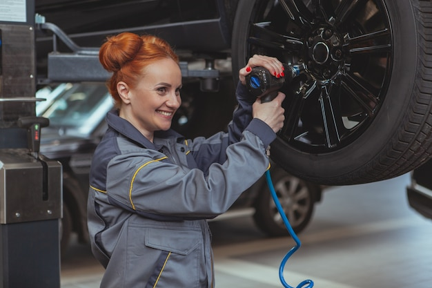 Weiblicher mechaniker, der an der autotankstelle arbeitet