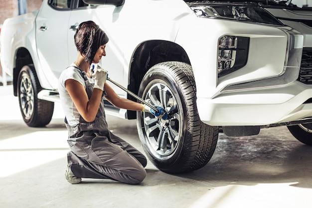 Weiblicher mechaniker der vorderansicht, der auto repariert