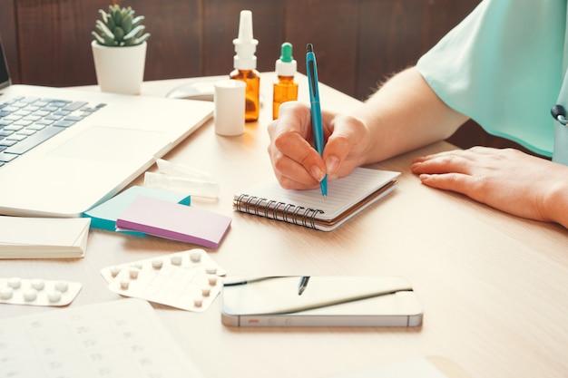 Weiblicher medizindoktor, der geduldiges medizinisches formular oder verordnung füllt