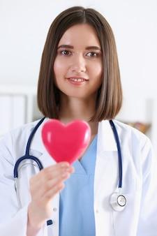 Weiblicher medizindoktor übergibt das halten und das bedecken der roten spielzeugherznahaufnahme. kardiotherapeutiststudenten-bildungsarzt machen herz-herzfrequenzmaßarrhythmiekonzept