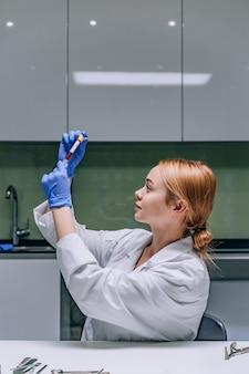 Weiblicher medizinischer oder wissenschaftlicher forscher, der ein reagenzglas in einem labor betrachtet.