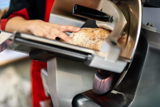 Weiblicher metzger, der yorkschinken in einer schneidemaschine schneidet