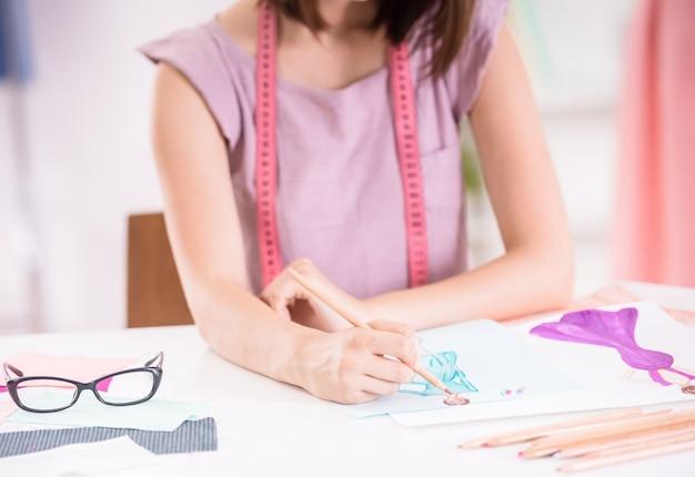 Weiblicher modedesigner, der im kleidungsstudio arbeitet.