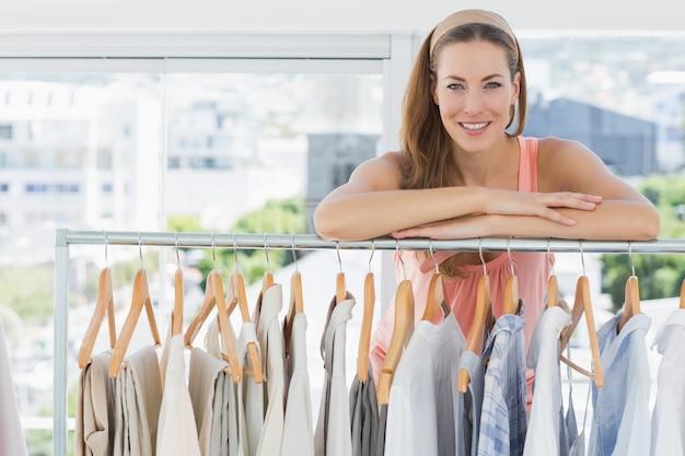 Weiblicher modedesigner mit gestell von kleidung im speicher