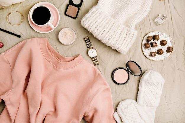 Weiblicher modelook mit stilvoller kleidung und accessoires. flache lage, draufsichtkomposition mit sweatshirt, kosmetik und kaffee.