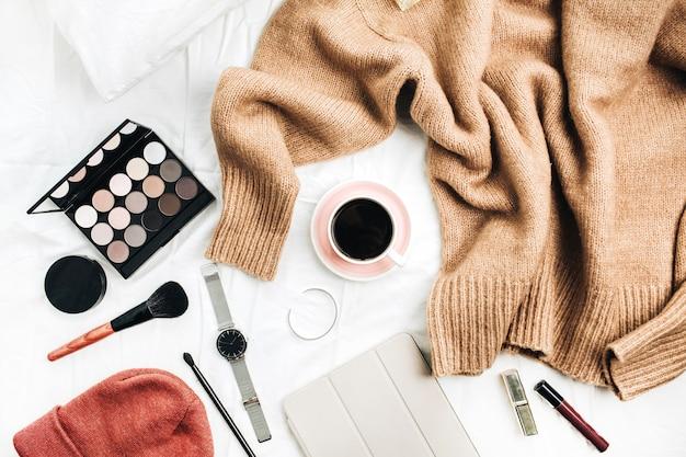 Weiblicher modelook mit stilvoller kleidung und accessoires. lifestyle-flat-lay-komposition mit pullover, kosmetik und kaffee.