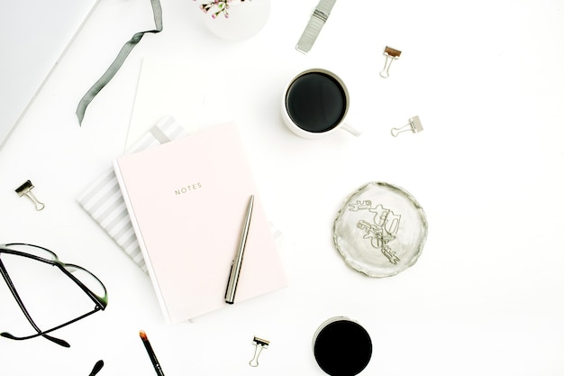 Weiblicher moderner home-office-raum mit pastellrosa notizbuch, brille, kaffeetasse, wildblumen und accessoires auf weißem schreibtisch. flache lage, ansicht von oben
