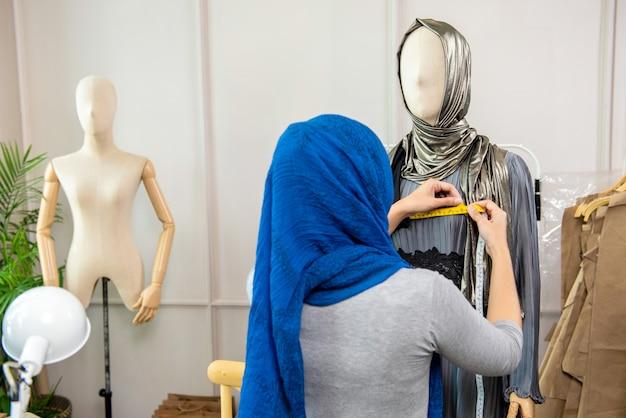 Weiblicher moslemischer designer, der ein mannequin misst