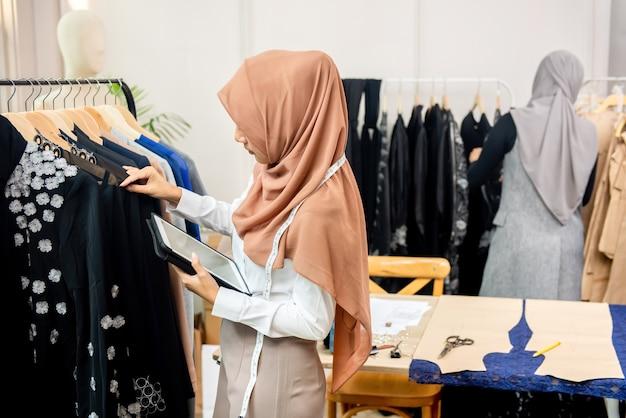 Weiblicher moslemischer designer, der gehangene kleidung im schneidershop überprüft