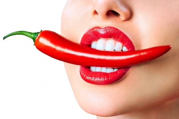 Weiblicher mund, der roten heißen chilipfeffer hält